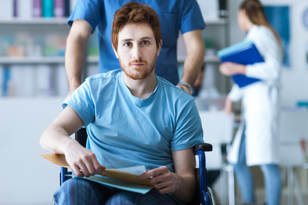 men at work: Disabled young man in wheelchair checking his medical records, a male nurse is pushing him, illness and healthcare concept Stock Photo