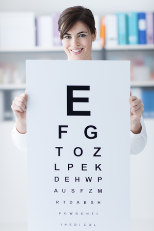 oculist: Female professional oculist holding an eye chart and smiling at camera, medical examination and eye care concept