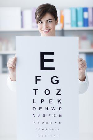 oculist: oculista profesional femenina que sostiene una carta de ojo y sonriendo a la cámara, el examen médico y el cuidado de los ojos concepto