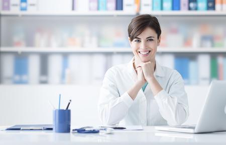 Jonge vrouwelijke arts die bij bureau werkt en bij camera glimlacht Stockfoto