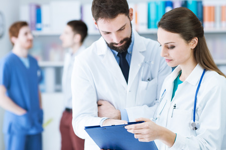 medical records: Doctors in the office checking patients medical records on a clipboard, teamwork and healthcare concept Stock Photo
