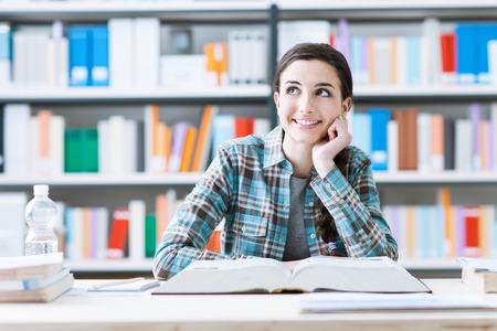 niña pensando: chica estudiante sonriente en la biblioteca estudiando y el día soñando, ella está pensando con la mano en la barbilla y mirando hacia arriba, la educación y el concepto de futuro