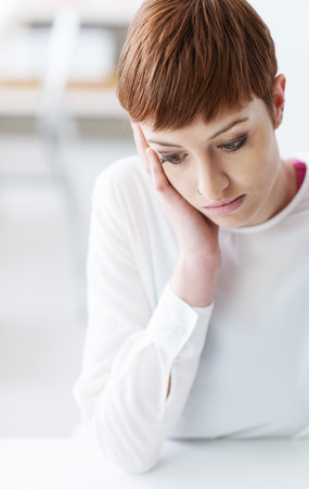 Sad young depressed woman sitting at desk and looking down, she is leaning on her hand, difficulty and emotional problems concept