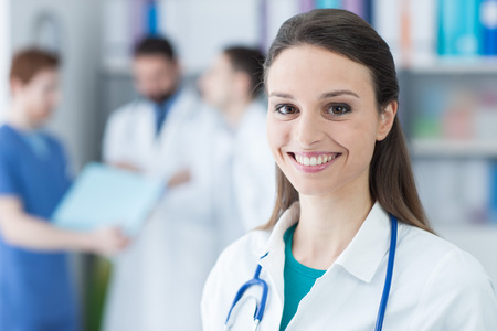 Smiling female doctor posing in the office and looking at camera, medical team on the background, healthcare concept