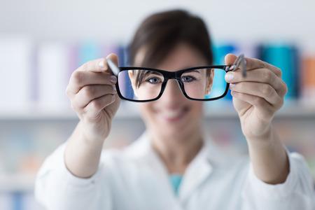 Optometrikus szemüveget ad a páciensnek, szemüveget előtérben, szemkontaktus, szelektív fókusz