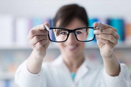 doctor giving glass: Optometrist giving eyewear to the patient, glasses on foreground, eye care concept, selective focus