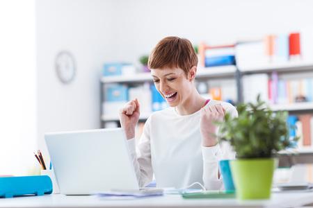 Enthousiaste femme qui a réussi à recevoir de bonnes nouvelles sur son ordinateur portable, gagnante et le concept de réalisation Banque d'images