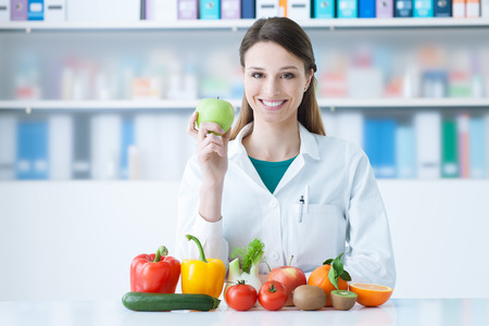 Smiling nutritionist in her office, she is holding a green apple and showing healthy vegetables and fruits, healthcare and diet concept Banco de Imagens