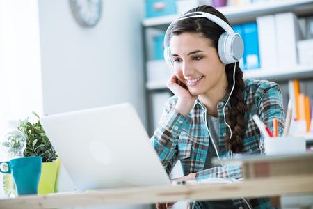 10 代の笑みを浮かべて少女ラップトップを使用と身に着けているヘッドフォンは、技術とレジャーの概念