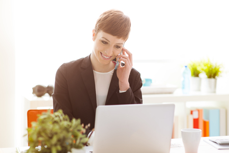 Successful confident businesswoman in her office using a smart phone and having a phone call