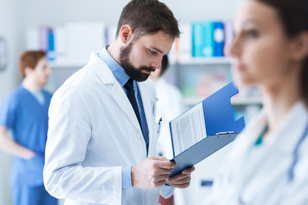medical records: Confident doctor checking medical records on a clipboard in his office, medical staff on the background, healthcare concept Stock Photo