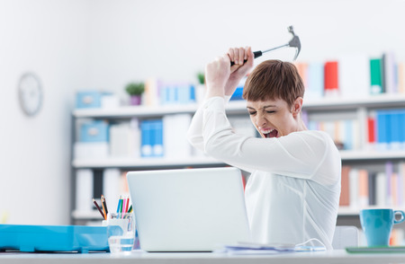 overwork: Stressed woman screaming and destroying her laptop with an hammer, computer problems and overwork concept Stock Photo