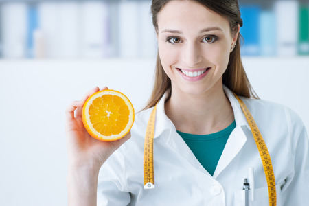 Smiling nutritionist holding a sliced orange, vitamins and healthy diet concept