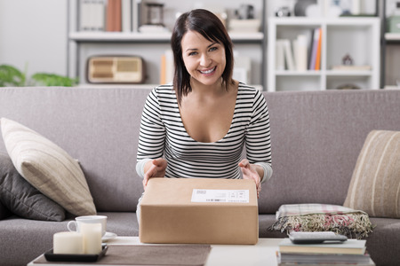 Smiling young woman at home on the couch, she has received a postal parcel, online shopping and delivery concept Banco de Imagens