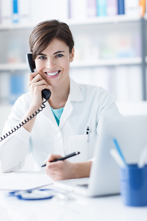 answering phone: Young female doctor working at office desk and answering phone calls Stock Photo