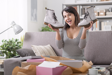 Cheerful young woman at home receiving a parcel with fashion shoes inside, online shopping and delivery concept