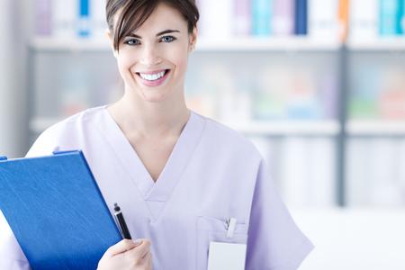 医療レポート、医療従事者を保持しているオフィスでの笑みを浮かべての若い女医