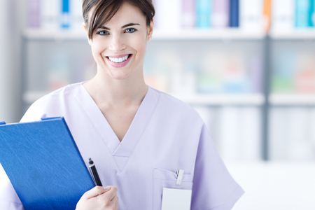 Smiling female young doctor in the office holding medical reports, healthcare professionals