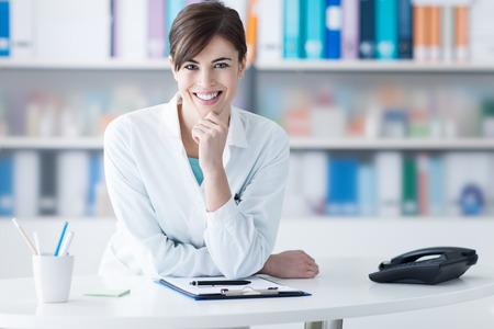 Aantrekkelijke jonge vrouwelijke arts leunend op de kliniek receptie met de hand op de kin, ze lacht naar de camera, de medische staf en de gezondheidszorg concept
