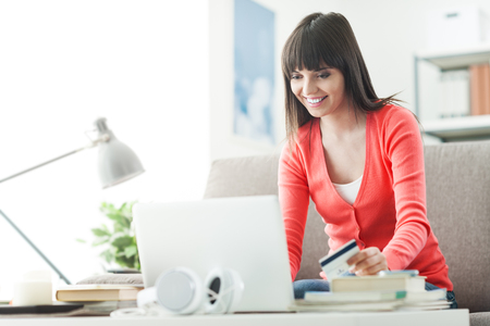 commerce communication: Young smiling woman at home using a laptop and shopping online with a credit card, commerce and communication concept Stock Photo