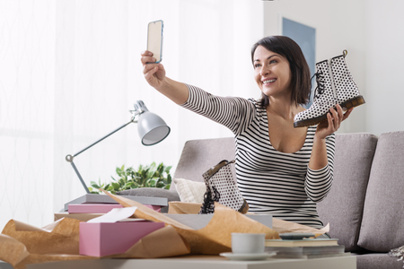 delivery box: Smiling woman unboxing a postal parcel and taking a selfie with her new purchases using a smartphone
