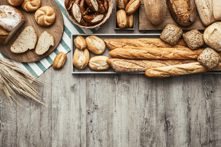 bread basket: Freshly baked delicious bread on a rustic wooden worktop with copy space, healthy eating concept, flat lay