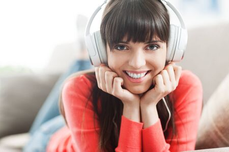 camera girl: Young smiling woman relaxing and listening to music with headphones