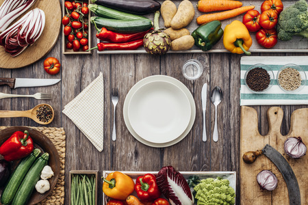 table set: Fresh healthy vegetables, chopping boards and cooking utensils composing a frame on a vintage kitchen worktop, table set at center Stock Photo