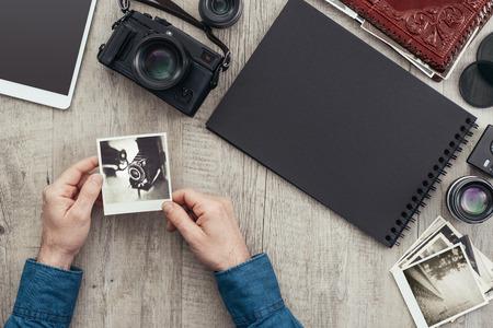 Matériel photo et caméra sur un bureau, un photographe tient une photo et crée un album photo Banque d'images