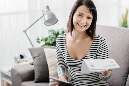 Smiling woman checking her cheap household and power bills, she is using a digital tablet