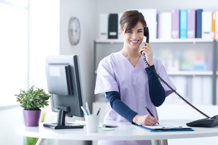 クリニックの受付で働く若い開業医医師彼女は電話に答えると予定をスケジュール 写真素材