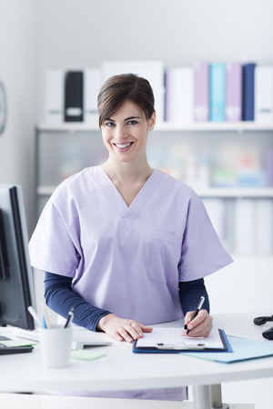 front office: Smiling female doctor wearing a scrub and working at the hospital reception, she is writing a medical report on a clipboard and scheduling appointments