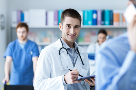 medical records: Doctor checking medical records and holding a clipboard, he is smiling at camera, medical staff on the background Stock Photo