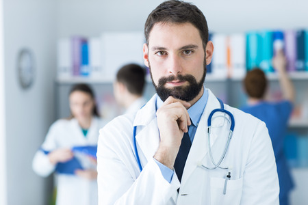 pathologist: Confident young doctor posing in the office, he is smiling at camera with hand on chin, medical team on the background