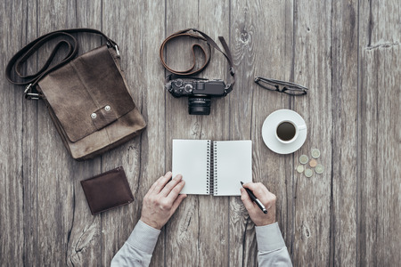 photojournalist: Photographer having a relaxing coffee break, he is writing down notes on a notebook Stock Photo