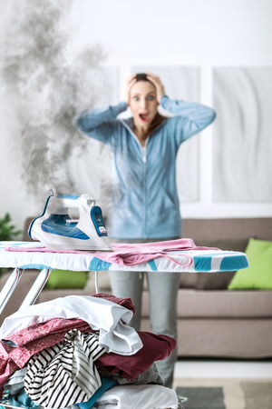 Shocked woman gasping at home, she has left the iron on and she is burning her clothes