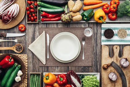 Fresh healthy vegetables, chopping boards and cooking utensils composing a frame on a vintage kitchen worktop, table set at center Stock Photo