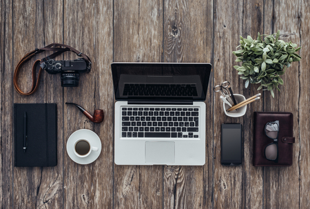 Hipster wooden desktop with laptop, camera, pipe and office accessories, flat lay banner