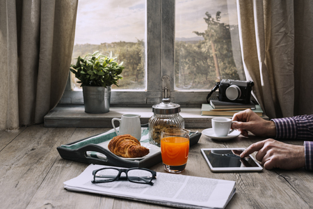 old windows: Hipster man having an healthy breakfast in a country house, he is using a digital tablet in front of a window, lifestyle and technology concept