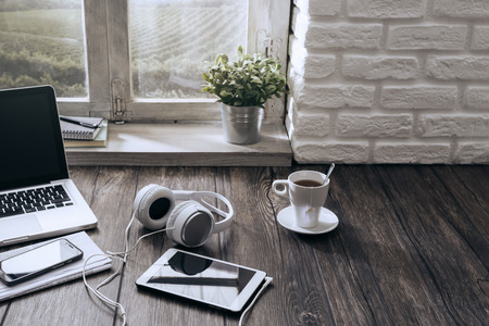 wooden window: Laptop, tablet and headphones on a wooden desktop next to a window, music and leisure concept Stock Photo