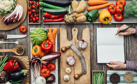 Freshly harvested vegetables, cooking utensils and chopping boards on a rustic kitchen worktop, a cook is writing recipes on a notebook Stock Photo