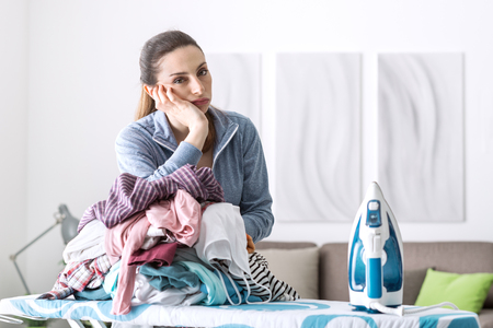 ironing board: Disappointed unhappy housewife leaning on a pile of laundry on the ironing board Stock Photo