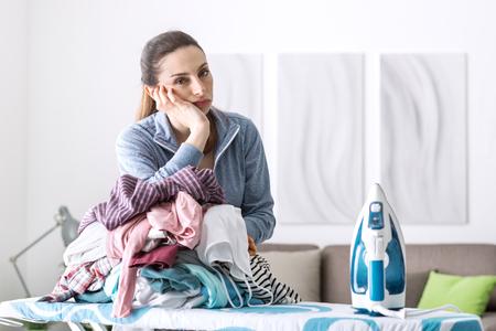 Decepcionado ama de casa infeliz que se inclina en una pila de ropa sobre la tabla de planchar