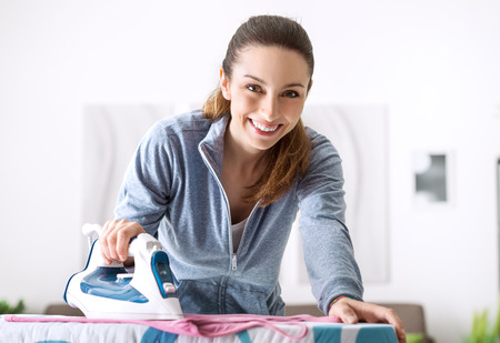 carefully: Efficient housewife ironing carefully her clothes, chores and houseworks concept Stock Photo