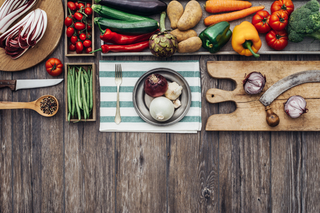 rustic kitchen: Fresh vegetables, chopping boards and utensils on a vintage kitchen worktop, healthy eating and cooking concept Stock Photo