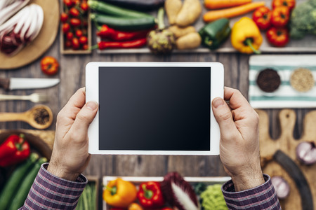cocina saludable: Hands holding a digital touch screen tablet, healthy vegetables and kitchen utensils on the background, nutrition and cooking concept Foto de archivo