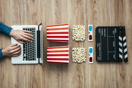 broadcasting: Man watching a film streaming online with popcorn, 3D glasses and clapboard, cinema and entertainment concept, flat lay Stock Photo