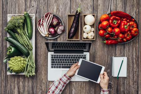 green and purple vegetables: Green, red, purple, white vegetables on a rustic kitchen worktop and hands using a digital tablet, healthy eating and technology concept, flat lay
