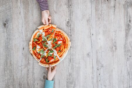 woman eat: Friends sharing a delicious pizza on a rustic table, they are holding a slice, top view Stock Photo