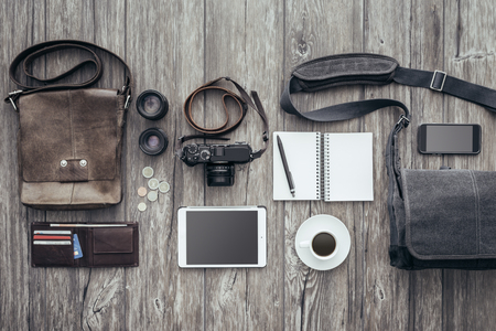 photojournalist: Photoreporter travel equipment with camera, tablet and bags, flat lay banner Stock Photo